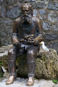 Seamus the Seagull beside statue of bearded man holding birds in his hands, Ottó Herman, founder of the Hungarian Ornithology Centre