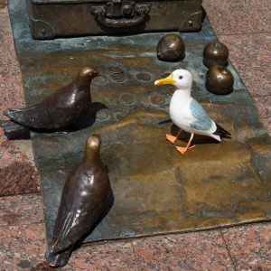 Seamus the Seagull on bronze sculpture with pigeons, apples, suitcase in Szeged, Hungary