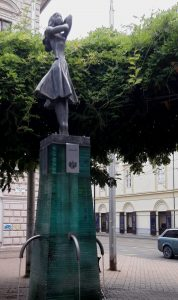 Anna thermal fountain in Szeged, Hungary, girl standing on top of fountain with water running from three taps