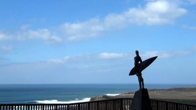 Sculpture of surfer with surfboard on cliff top at Ericeira Portugal