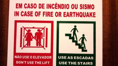 Warning sign on elevator in English and Portuguese