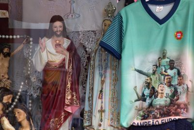 religious statues and football shirts in shop window in Fatima Portugal