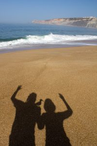 Shadow of man and woman with Seamus the Seagull waving on beach at Nazaré Portugal