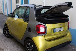 Surfboard in bag protruding from back of gold Smart car