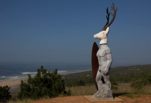 Sculpture of surfer with stag's head at cliff top at Nazaré Portugal