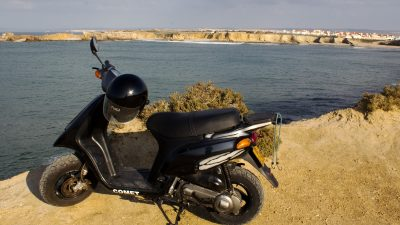 Black scooter parked on cliff top