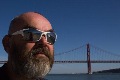 head of bald man with grey beard wearing white sunglasses with river and suspension bridge, blue sky in background