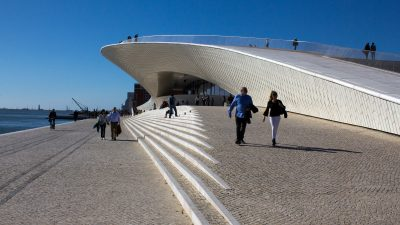 people walking in front of modern white curved building on bank of river, MAAT Museum, Lisbon