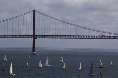 numerous small yachts and dinghies in front of large suspension bridge, coastline in background, 24th April Bridge over Tagus, Lisbon, Portugal