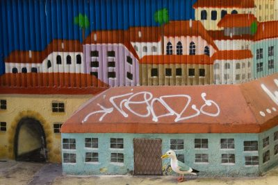 Seamus the Seagull standing in front of mural of rows of colourful houses