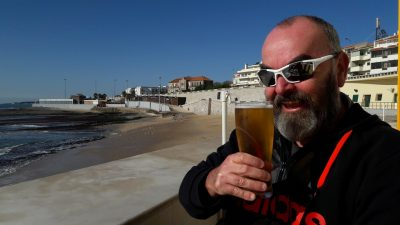 Smiling man with pint of beer in hand at beach