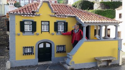 Woman in red coat standing on steps of model house, Seamus the Seagull on balustrade, Portugal dos Pequenitos, Coimbra