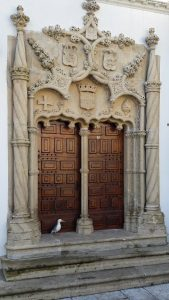 Seamus the Seagull standing at scale model doorway of University Chapel, Portugal dos Pequenitos, Coimbra
