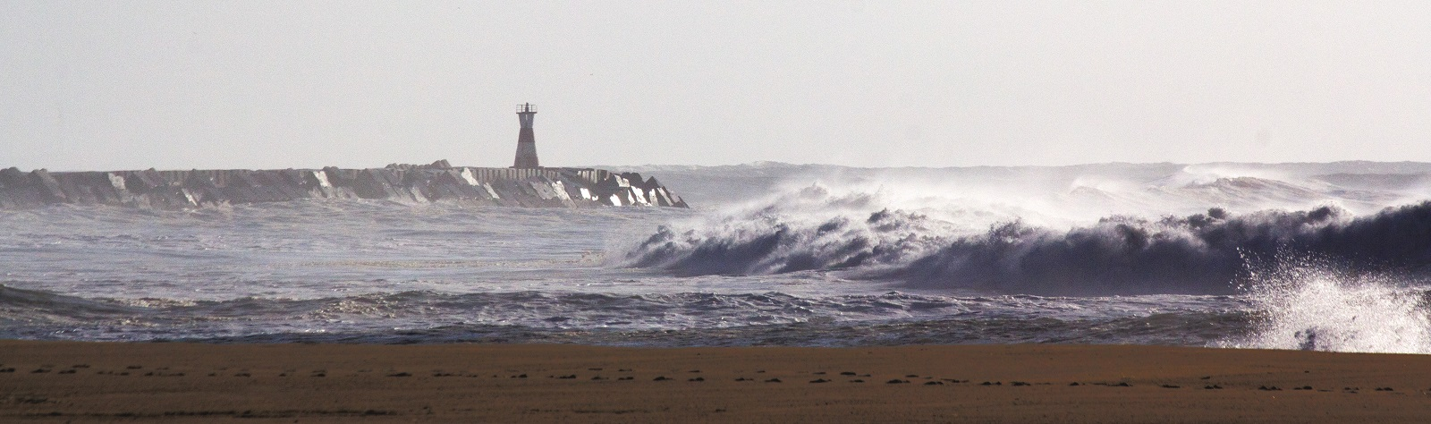 waves crashing on beach, pier with lighthouse at end, Figueira da Foz, Portugal