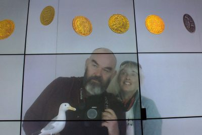 Seamus the Seagull with man and woman on video screen with falling gold coins in Money Museum Lisbon