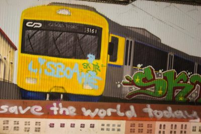 Mural of suburban train with buildings, graffiti, Alcantara train station, Lisbon