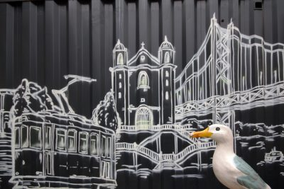 Seamus the Seagull with mural of Lisbon sights