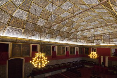 Ceremonial hall with elaborately decorated ceiling, chandeliers, portraits on walls, Coimbra University, Portugal