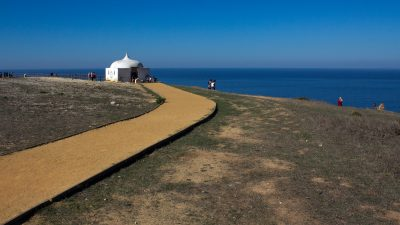 footpath leading to small white chapel with domed roof coming to a point on cliff top, ocean and blue sky in background, Ermida da Memoria, Cabo Espichel, Portugal