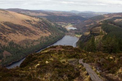 bog land with board walk with panoramic view of two lakes in deep valley with more mountains in background, Spinc mountain, Glendalough, County Wicklow, Ireland
