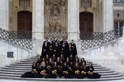 Group of graduates dressed in black gowns holding certificates with yellow ribbons, standing and sitting on steps in front of palace, Coimbra University, Portugal