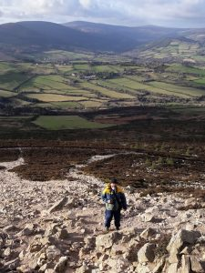 Man in winter clothing standing on rocky slope with green fields and hills in background, County Wicklow, Ireland