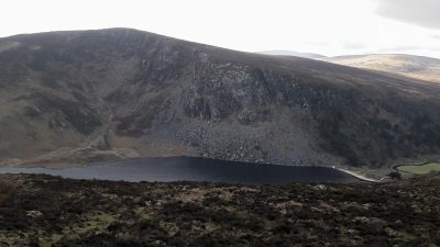 dark lake in with white beach in deep valley, more hills in background, Lough Tay, Guinness Lake, Luggala, County Wicklow