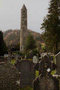 Graveyard with celtic crosses in foreground with tall round tower and trees and hills in background, Glendalough, County Wicklow, Ireland