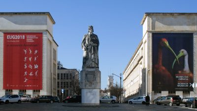 Statue of King Dinis in square with university buildings in background, Coimbra, Portugal