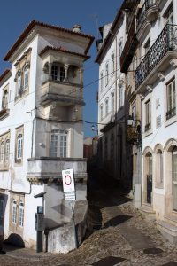 Steep narrow street between old tall narrow buildings in old town centre, Coimbra, Portugal