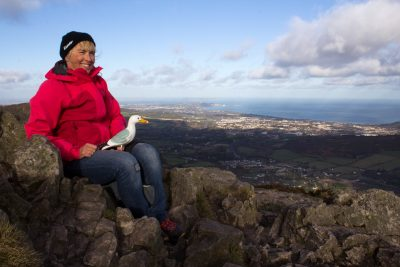Woman wearing red anorak, blue jeans and black hat sitting on mountain summit, Seamus the Seagull on her lap, view of Dublin bay in background, Great Sugar Loaf Mountain, Wicklow, Ireland