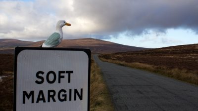 Seamus the Seagull on sign 'Soft Margin' by country road with bogs and hills in background, Sally Gap, County Wicklow, Ireland