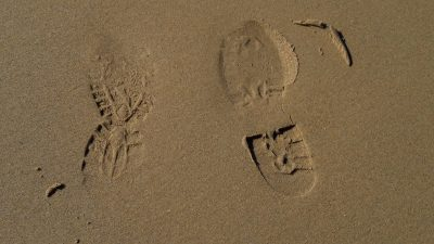 impressions of running shoes in sand