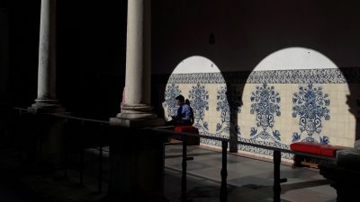 Man sitting on red bench in corridor with arches, blue and white tiles on wall, Coimbra University, Portugal