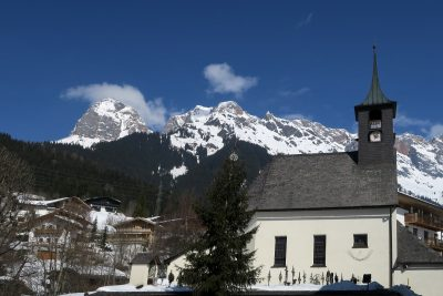 church with graveyard in Austrian villaage with high snow-covered mountains in background with blue sky and a few clouds, Hinterthal, Maria Alm, Salzburg, Austria