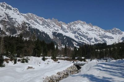 high snow covered mountains in background with trees, river with bridge and snow covered areas in foreground, Hochkönig massif, Hinterthal, Maria Alm, Salzburg, Austria