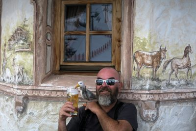smiling bald man with beard wearing dark tshirt and sunglasses holding pint of beer and Seamus the Seagull seated in front of building with window, with painted rustic scenes, reflection of ski slope in window