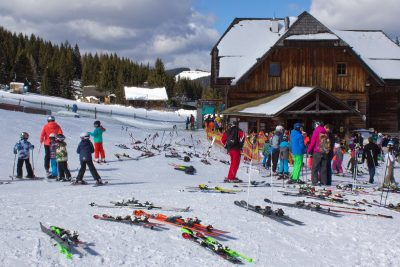 Wooden buildings, skiers in brighly coloured outfits, standing around and queuing for ski lift, numerous pairs of skis placed around the area, trees, hills in background, Höldahütten, Sommeralm, Styria, Austria