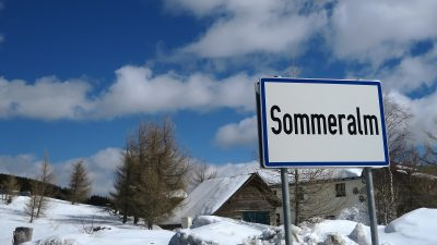 buildings and trees in snow covered landscape in mountains, sign in foreground reads Sommeralm, Sommeralm, Almenland, Styria, Austria