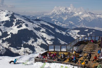 large wooden retaurant terrace on mountain peak with skiers sitting at tables and on sun loungers with panoramic view of snow covered mountain range, Maria Alm