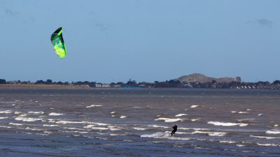 Kite surfer with green and yellow kite on waves, coastline with hill in background, Dollymount Strand, Bull Island, County Dublin