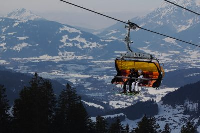 two skiers sitting on chairlift en route up mountain, snow covered mountains in background, Hinterthal Maria Alm