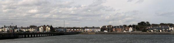 view of coastline with bridge to left, elegant villas the length of coast, from Bull Island, County Dublin