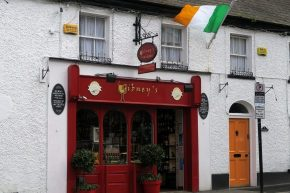 Red shop front, Gibney's in white two storey building with yellow door, Irish flag flying from flagpole high on wall, Malahide, County Dublin