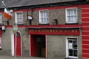 Grey pub with red doors and signage, John Gibney & Sons, Irish flag flying from flagpole on second storey, Malahide, County Dublin