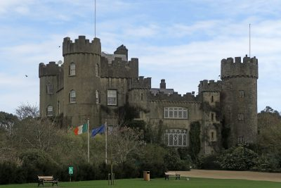 large grey castle with numerous towers, Irish and EU flags flying in foreground, Malahide Castle, County Dublin